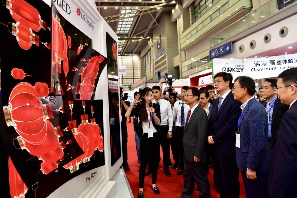 LG Display's vice president Lee Cheol-gu (front row, second from right) and Vice President Wang Zhi-jun of the Chinese Ministry of Industry and Information Technology (front row, fourth from right) are seen examining a piece of art created with OLED technology at the 'CITE2019' exhibition held in Shenzhen. 출처 : 전자부품 전문 미디어 디일렉(http://www.thelec.kr)